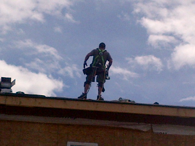 roofer tied off using harness on roof